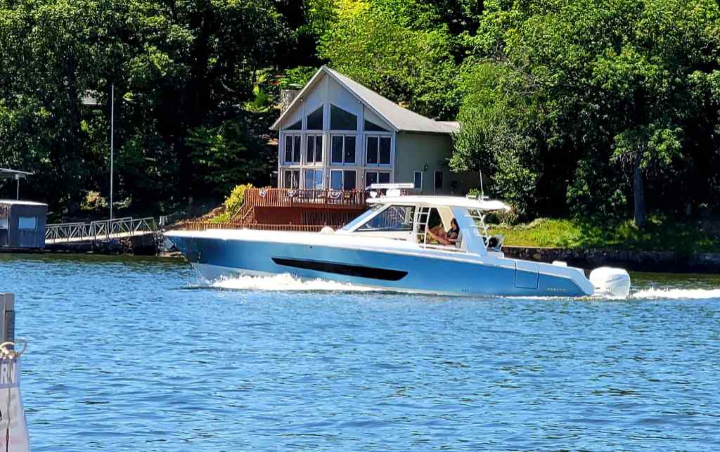 Cabin boat cruises by on Lake of the Ozarks upon leaving some boat slips near me